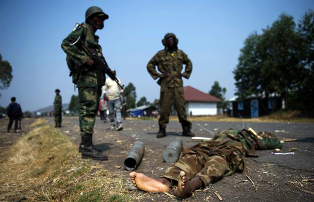 PHIL MOORE [AFP] - Soldats de l'armée congolaise se tiennent à côté d'un corps d'un prétendu M23 combattant dans Kanyarucinya, à environ 12 kms de Goma, dans l'est de la République démocratique du Congo le 16 Juillet 2013.