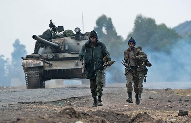 PHIL MOORE [AFP] - Soldats de l'armée congolaise à pied devant un    char de combat à travers Kanyarucinya, à environ 10 km de Goma, dans l'est de la République démocratique du Congo le 17 Juillet 2013