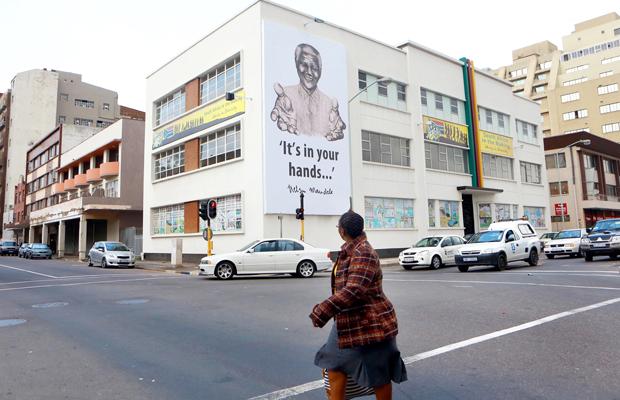 RAJESH JANTILAL [AFP] - Une immense banderole de l'ancien président Nelson Mandela plane au-dessus de l'Hindu Tamil Instituite à Durban le Juillet 17,2013 en préparation pour célébrer le 95ème anniversaire de Nelson Mandela et à commémorer la Journée internationale Nelson Mandela, le 18 Juillet