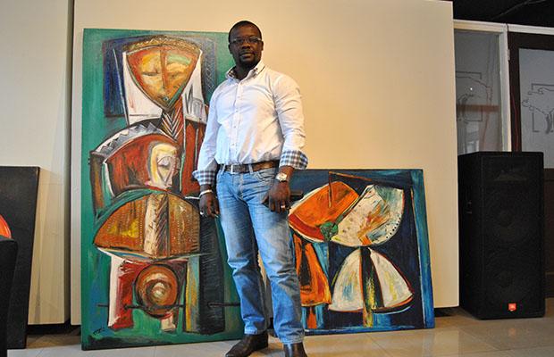 Le peintre Franck Dikisongele devant quelques uns de ses tableaux.