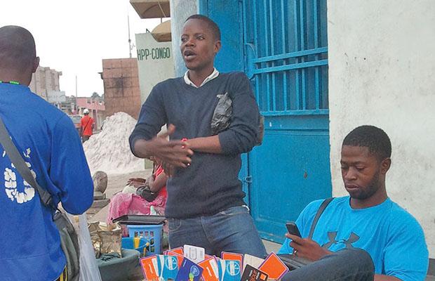 Un  « cambiste » et vendeur de cartes téléphoniques à Kintambo-Magasin.