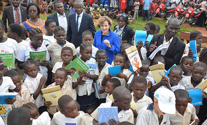 Des eleves de Kanzi brandissant leurs manuels scolaires sous les regards de Maker Mwangu Famba et d'Alice Albright