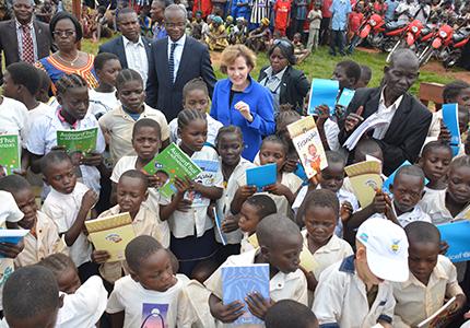 feature__0017_legende_Des eleves de Kanzi brandissant leurs manuels scolaires sous les regards de Maker Mwangu Famba et